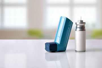 Cartridge and blue medicine inhaler in a room front view