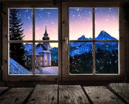 Blick aus dem Fenster einer Holzhütte auf eine Winterlandschaft mit kleiner Kirche