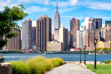 The midtown Manhattan skyline in New York City on a beautiful summer day seen from a park in Queens