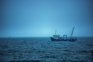 Trawler fishing boat sailing in open waters on a cold and foggy