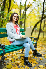 Young happy girl students  working on laptop in autumn park