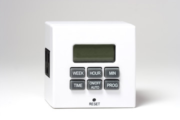 White plug-in timer for electrical items. white background. Mainly used for turning lamps and lights on and off. Horizontal.