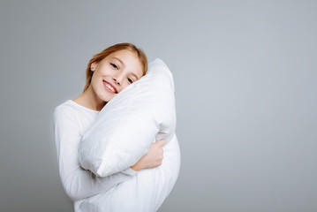 Positve cute girl holding head on the pillow