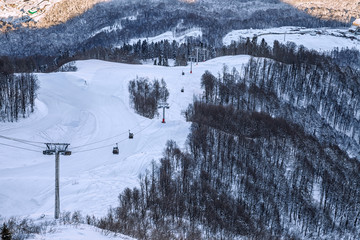 Cableway ski lift gondola cabins of Krasnaya Polyana resort on mountain slope background at sunset beautiful winter scenery