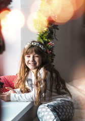 Kid girl having fun near windowsill in christmas time