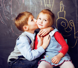 little cute boy kissing blonde girl in classroom at blackboard, first school love, lifestyle people concept