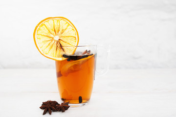 Cup of tea with orange and cinnamon on white background, free space. Glass of hot spiced winter drink with anise stars, free space for text