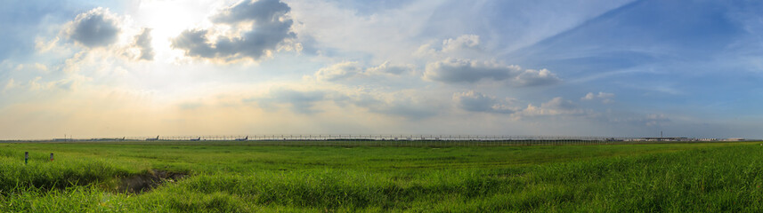 Panorama scene of green grass field with blue cloudy sky in evening with airplanes background.