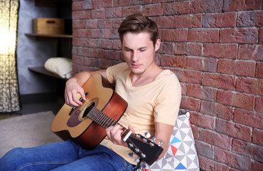 Young man playing guitar and sitting on the floor