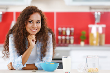 Beautiful young African-American woman having breakfast with milk in the kitchen