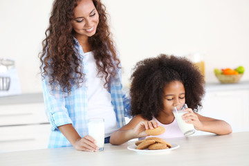 African-American mother and daughter drinking milk for breakfast in the kitchen