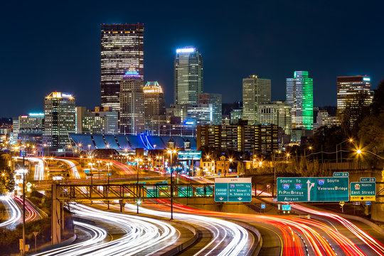Pittsburgh skyline by night. The rush hour traffic leaves light trails on I-279 parkway