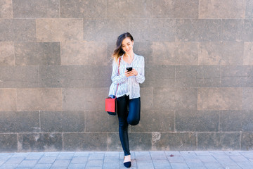 Woman holding a cell phone, standing outdoors Wall mural
