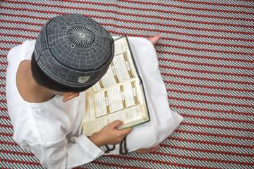 Boy reading Quran.