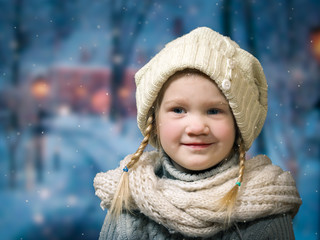 Wonderful little girl under falling snow, snowflakes. The good, happy child's smile. Portrait