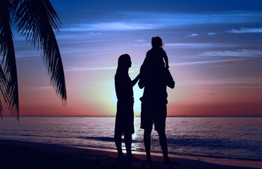 Happy family with little daughter together at sunset
