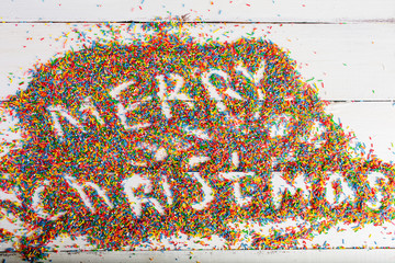 Christmas background. Merry Christmas written with color sprinkling on turquoise wooden background