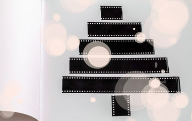 Stylized Christmas tree of a film strips on the white page of an album with drawn snowflakes , background for Christmas and New Year holiday greetings