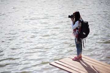 Young asian girl taking photo outdoors with digital camera.