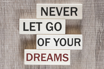 Never let go of your dreams. Motivational quote written on wooden tiles