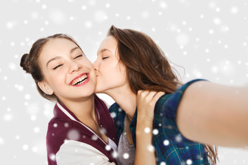 happy teenage girls taking selfie and kissing