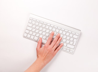 Typing femle hand on keyboard over white