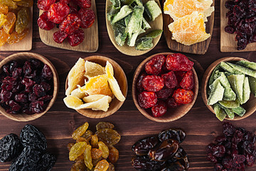 Assortment of dried fruits in spoons, bowls on brown wooden background. Decorative border of dry exotic fruit. Top view.