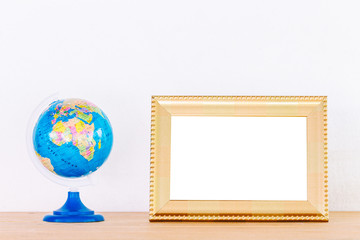Photo frame and global ball toy on wooden table