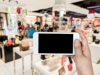 Hand holding mobile smart phone on fashion shoes and bags shoppi