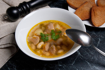 Bean soup in white plate with metal spoon, several toast on whit