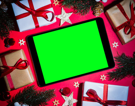 Tablet and tablet in Christmas red background with tree, gift an
