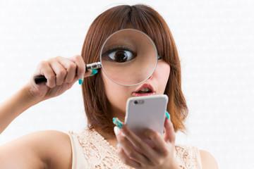スマートフォンを虫眼鏡で見る女性