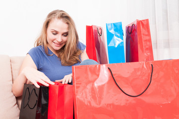Lady sitting on couch looking in her shopping bags