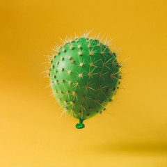 Balloon with cactus needles on bright yellow background. Creativ