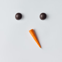 Snowman face made of cookies and carrot. Minimal holiday concept