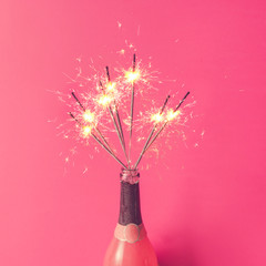 Champagne bottle with sparklers on pink background. Flat lay.