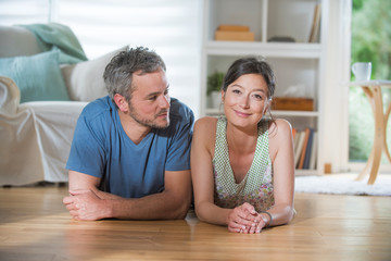 At home, a nice couple in their thirties lying on wooden floor