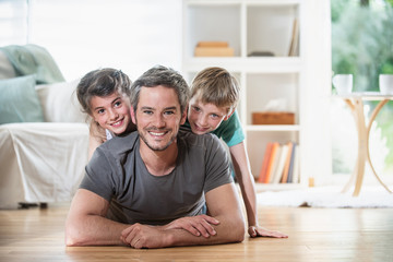 At home, Dad and kids lying on wooden floor in the living-room