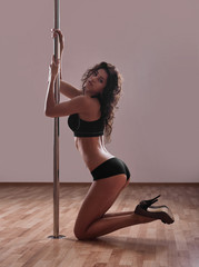 Flexible sexy girl dancing in black lingerie on the pole horizontal picture