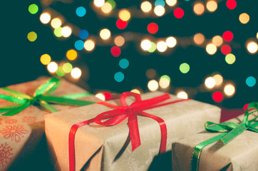Christmas card. Holiday gift boxes on the bright blurred Xmas li
