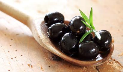 schwarze Oliven auf Kochlöffel