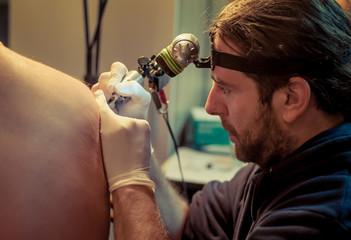 Artist making tattoo on male customer