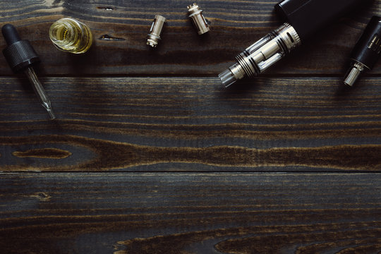 Vaping set with copy space on the wooden background.