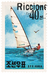 Sailing yacht in the sea on postage stamp
