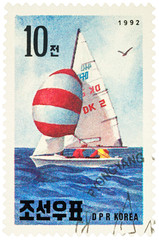 Sailboat in the sea on postage stamp