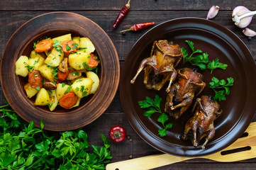 Roasted quail on a spit on a ceramic bowl with greens. Baked potato. The top view. Holiday menu.