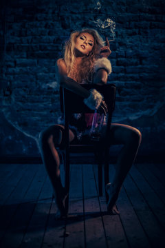 The bad girl with a bottle of whiskey sitting on a chair, and smoking. The room is dark and scary.