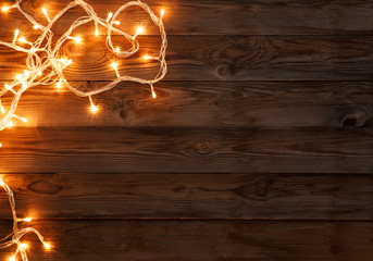 Christmas dark brown wooden background decorated with shining lights