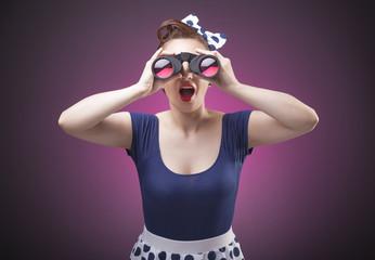 Pretty Pin Up girl loking through binoculars on pink background