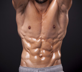 Cropped image of athletic man showing sixpack abs over black bac